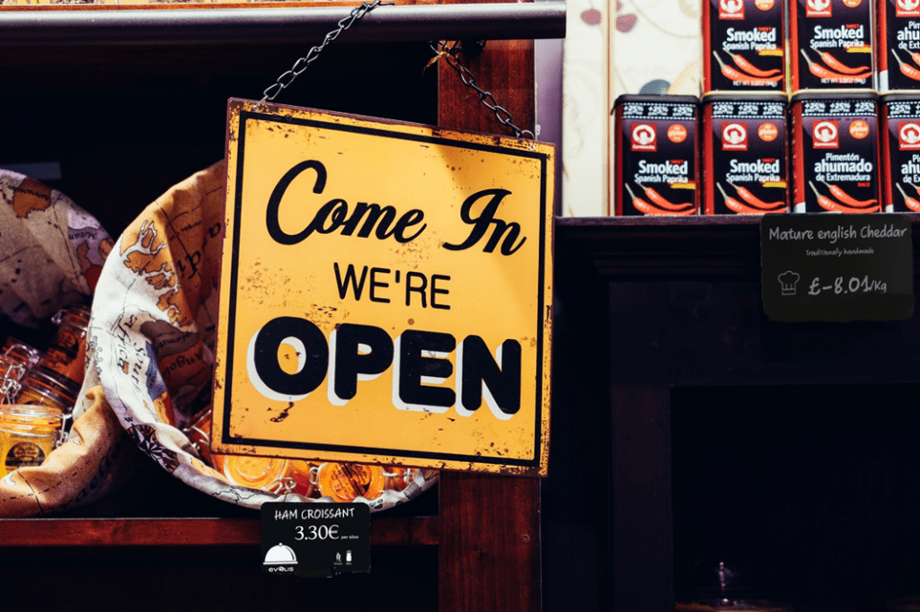 Sign in shop window reads 'Come In, We're Open'